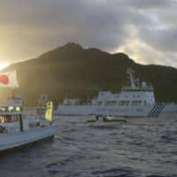 A Chinese maritime surveillance vessel (center back) passes near Uotsuri Island, part of the disputed Senkaku Islands in the East China Sea, in July 2013. | KYODO