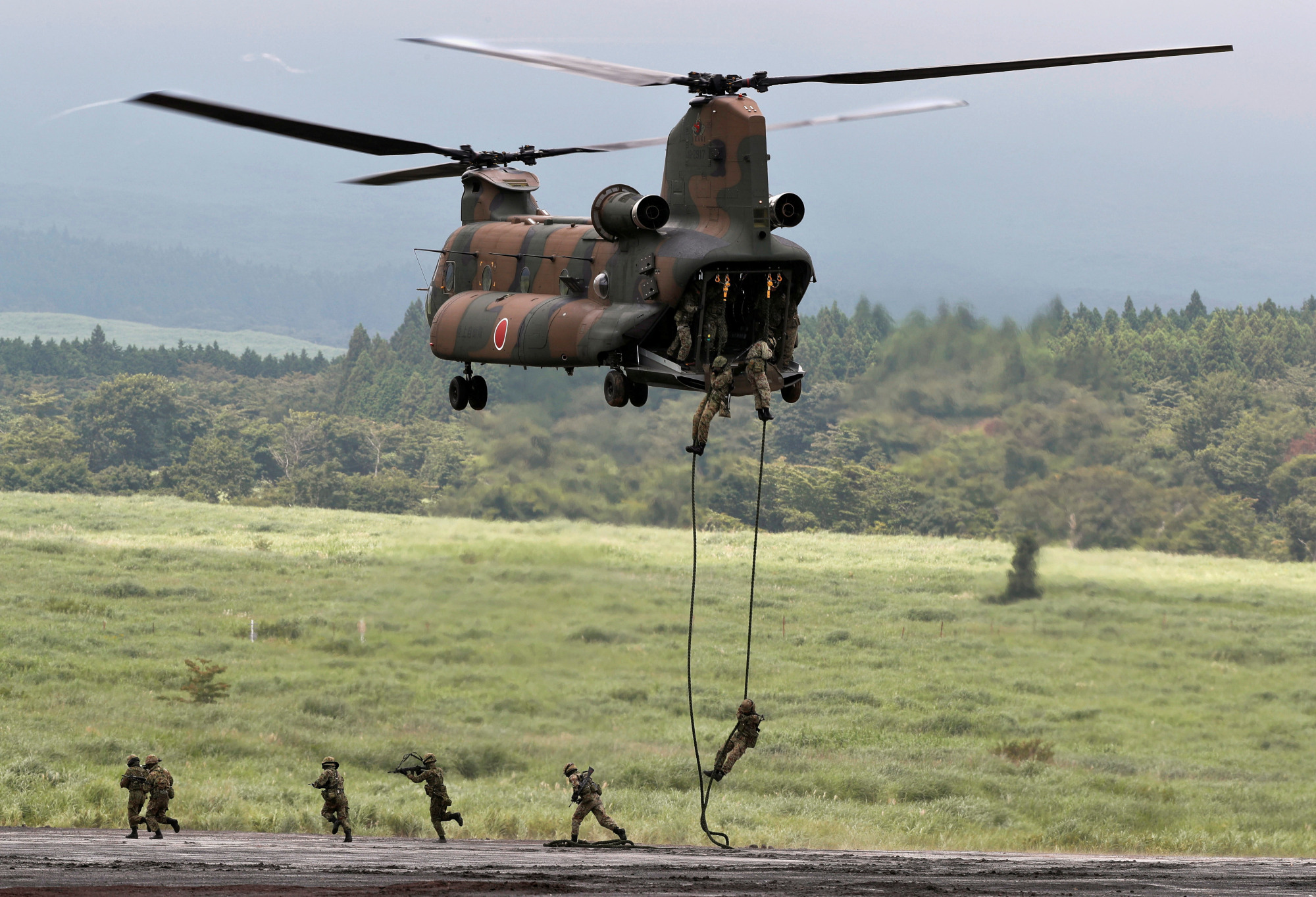 Ground Self-Defense Force soldiers rappel from a CH-47 Chinook helicopter during an annual training session near Mount Fuji at Higashifuji training field in Gotemba, Shizuoka Prefecture, on Aug. 22. | REUTERS