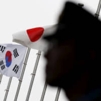 A police officer stands guard near Japanese and South Korean national flags at a hotel where the South's Embassy in Japan held a reception to mark the 50th anniversary of normalization of ties between Seoul and Tokyo, in the Japanese capital in June 2015.   | REUTERS