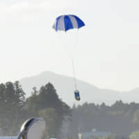 A robot attached to a parachute descends during a test as part of a project to create a space elevator, conducted in Minamisoma, Fukushima Prefecture, on Sunday. | KYODO