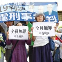 Evacuees from Fukushima Prefecture on Thursday hold up a banner reading 'Not guilty: Unjust ruling' after the Tokyo District Court acquitted three former executives of the operator of the Fukushima No. 1 nuclear power plant. | KYODO