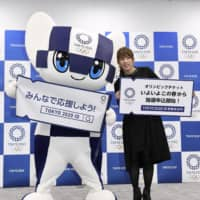 Retired wrestler Saori Yoshida poses with Miraitowa, the official mascot of the 2020 Tokyo Olympics, in Tokyo on Jan. 30 at an event promoting the sales process for tickets for the games. | KYODO