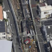 A derailed Keikyu Line train is pictured after it collided with a truck in Yokohama. | KYODO
