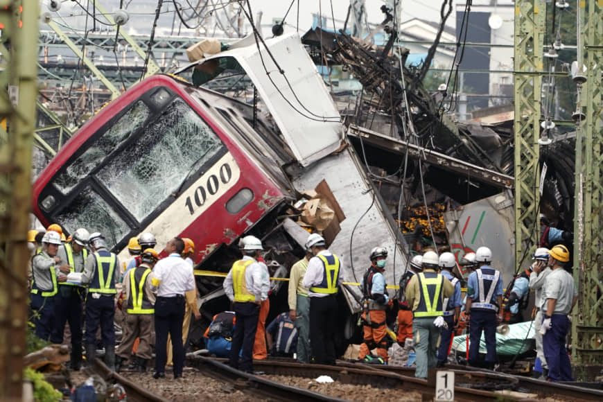 Police, railway and emergency personnel inspect a Keikyu express train that derailed after hitting a truck loaded with boxes of citrus in Yokohama on Thursday, killing one and injuring more than 30 others. | AP