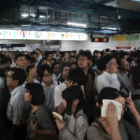 Commuters wait for platforms to open at Shinjuku Station on Monday, Typhoon Faxai's assault on the Kanto region earlier in the day left train services suspended.   AP