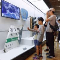 Children visit an exhibition about the 2011 tsunami disaster at a newly-opened museum in Rikuzentakata, Iwate Prefecture, on Sunday. The disaster devastated coastal towns and fishing communities in the Tohoku region on March 11, 2011. | KYODO