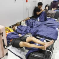 Travelers stranded at Narita Airport rest in sleeping bags provided by the airport operator on Monday night. | KYODO