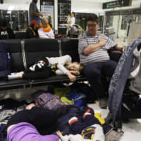 Stranded travelers wait at Narita Airport in the early hours of Tuesday, after the public transportation system connecting the airport and the Tokyo metropolitan area was disrupted in the wake of Typhoon Faxai. Around 13,000 people stayed at the airport overnight. | KYODO
