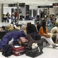 Stranded passengers at Narita International Airport try to settle in for the night on Tuesday in the wake of Typhoon Faxai. | KYODO