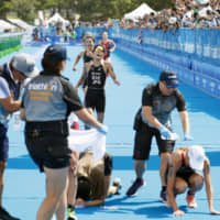 Triathletes arrive at the finish line during a competition held last month in Tokyo's Odaiba waterfront district. The scorching summer in the capital has become a headache for the organizers of the Tokyo 2020 Olympics, and Osaka will likely experience the same problems when it hosts the 2025 World Expo. | KYODO