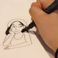 This is me: Christine Mari Inzer sketches a self-portrait at the offices of The Japan Times.   CHISATO TANAKA
