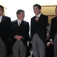 Prime Minister Shinzo Abe has kept newly appointed Foreign Minister Toshimitsu Motegi (second from left) in a position of leadership in every reshuffle since 2012. | BLOOMBERG