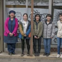 Linda Denis (left), an associate professor at Joshibi University of Art and Design, poses with students outside their converted ARToba gallery in Nakamachi. | STEPHEN MANSFIELD
