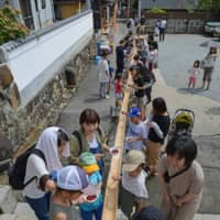 Children and parents enjoy food outside Sainenji temple. The nagashi somen event is held three or four times a year. | STEPHEN MANSFIELD