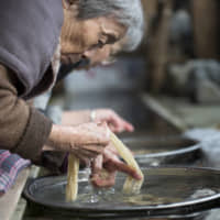 High standards: Clean, cold well water flows through the workshop. Here, Hagi Suzuki and Mariko Furuta perform the task of removing dirt from bark strips. Not even the slightest impurity can remain if Honmino-shi is to meet expectations. | MASASHI KUMA