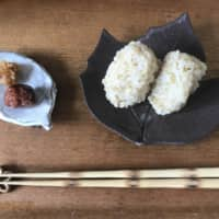 'I will have this meal': A pair of chopsticks sit horizontally in front of brown rice onigiri (rice balls) and a homemade pickled plum with miso. | MOMOKO NAKAMURA