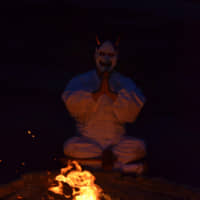 Fire sit with me: A man wearing a mask performs a ritual in front of a fire. | © NIHON JUJUTSU KENKYU JUKIKAI