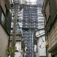Power lines clutter the skyline in an alley in Tsukishima, Chuo Ward. | ANDREW LEE