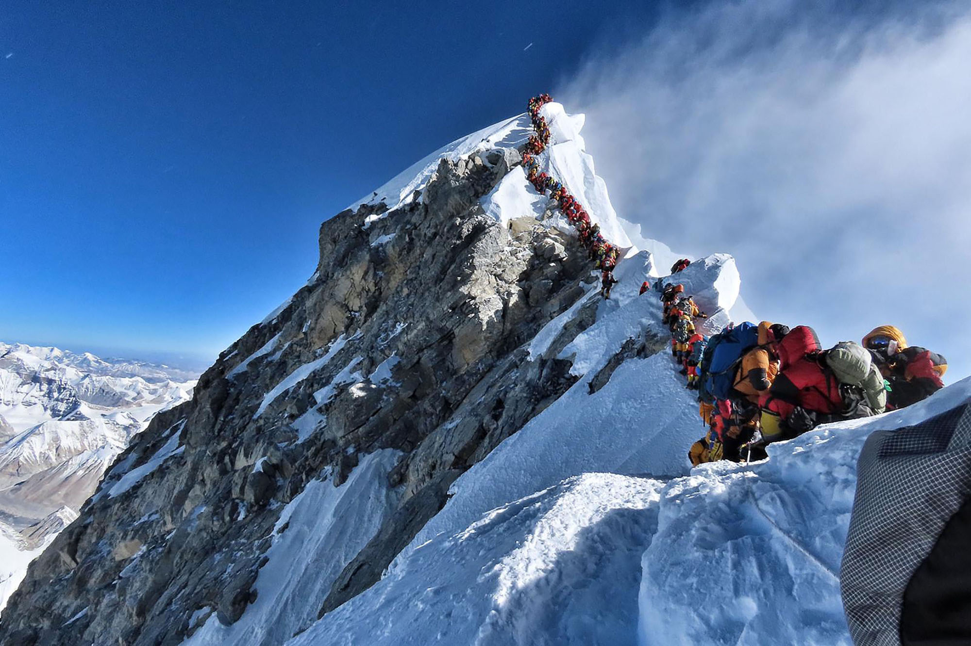 Dozens of climbers wait in line to reach the summit of Mount Everest on May 22. | AFP-JIJI