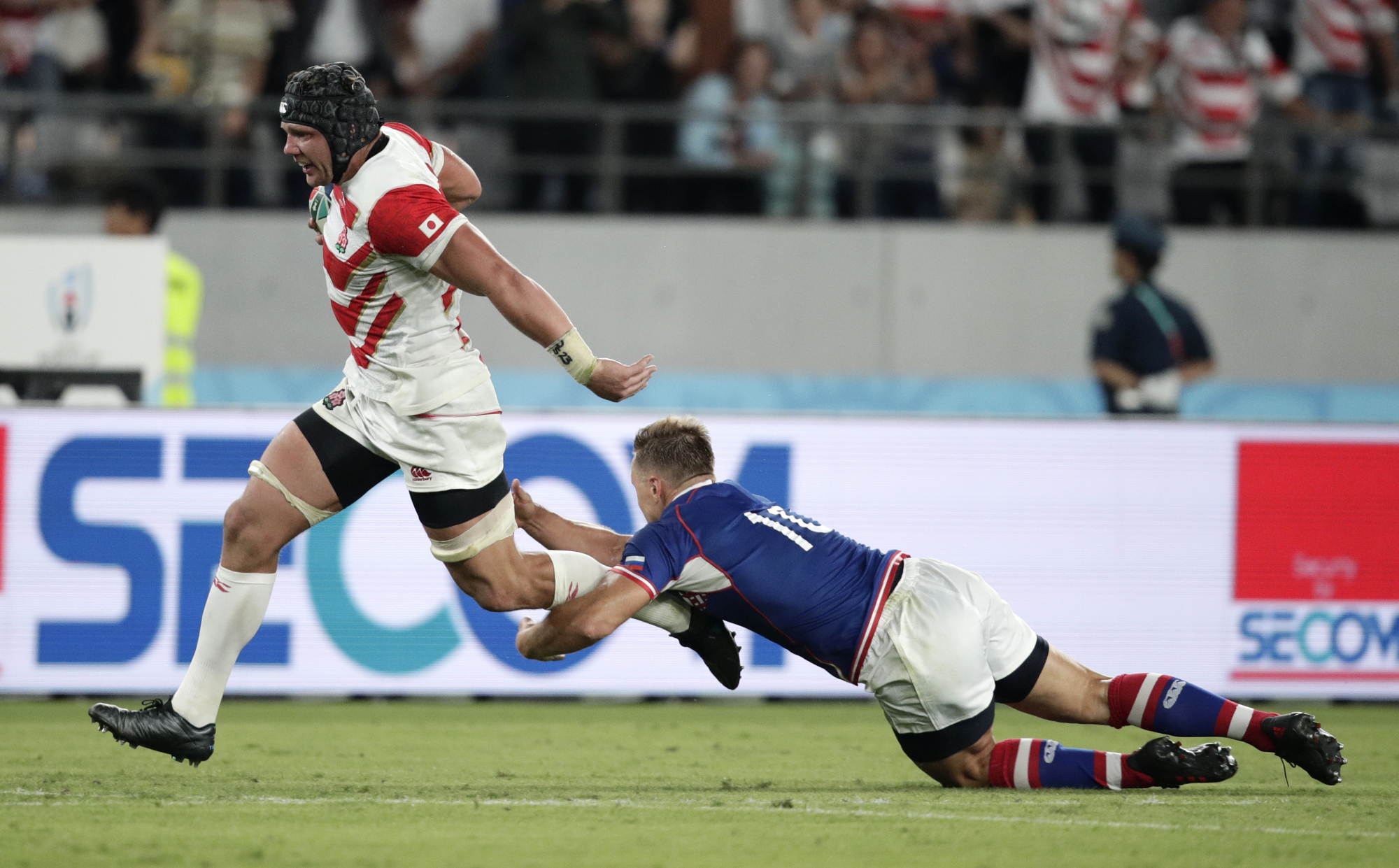 Japan's Pieter Labuschagne breaks the tackle of Russia's Yury Kushnarev on his way to scoring a try during the Rugby World Cup opening game at Tokyo Stadium on Friday night. Japan defeated Russia 30-10. | AP