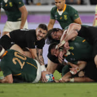 New Zealand's TJ Perenara (left) controls the ball after a tackle on Saturday. | AP