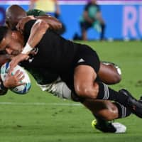 New Zealand flyhalf Richie Mo'unga is tackled by South Africa wing Makazole Mapimpi during their Rugby World Cup contest on Saturday in Yokohama. | AFP-JIJI