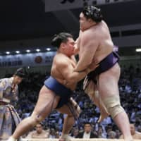 The 169-cm Terutsuyoshi (left) overcomes his size disadvantage to force out Yago, who stands 183 cm, at the Nagoya Basho in July at Dolphins Arena. | KYODO