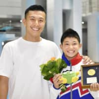 Rikuto Tamai (right), who at just over 13 became Japan's youngest national diving champion on Monday, poses with previous record holder and five-time Olympian Ken Terauchi on Monday in Kanazawa. | KYODO