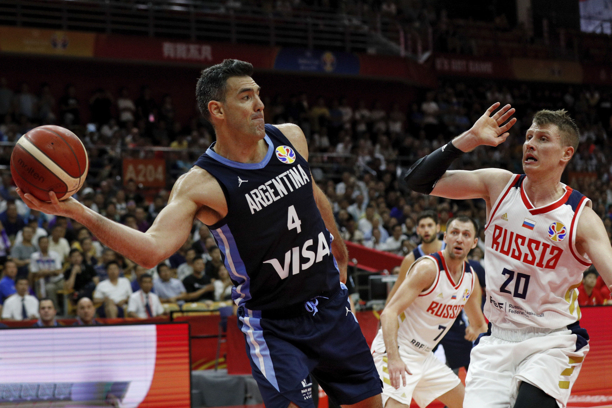Argentina's Luis Scola looks to pass under pressure from Russia's Andrey Vorontsevich in their Group B at the FIBA World Cup in Wuhan, China, on Wednesday. | AP