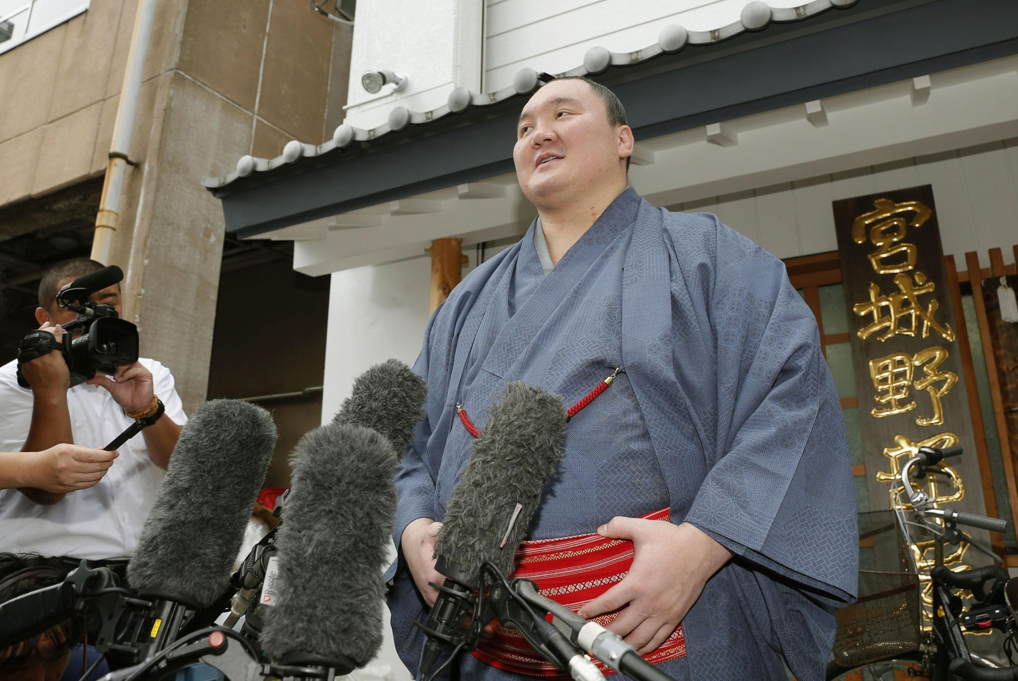 Hakuho speaks to reporters in front of his Miyagino stable in Tokyo on Tuesday, the day it was announced that he's become a Japanese citizen. | KYODO