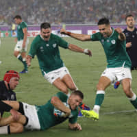Ireland's Andrew Conway (bottom center) scores a try during his team's Rugby World Cup pool stage win over Scotland on Sunday at International Stadium Yokohama.   AP
