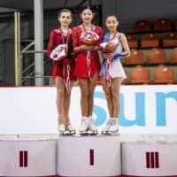 Bronze medalist Rino Matsuike (right) shares the podium with winner Lee Hae-in of South Korea (center) and second-place finisher Daria Usacheva of Russia at the Junior Grand Prix in Riga on Saturday night.   INTERNATIONAL SKATING UNION