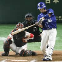 The Dragons' Nobumasa Fukuda hits a two-run double in the seventh inning against the Giants on Thursday night at Tokyo Dome. Chunichi rallied to beat Yomiuri 3-2. | KYODO
