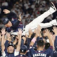 The Lions players toss manager Hatsuhiko Tsuji into the air for the traditional doage after their 12-4 victory over the Marines on Tuesday night in Chiba. Seibu clinched the Pacific League pennant for the second straight year. | KYODO