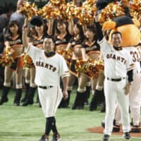 Retiring Giants star Shinnosuke Abe (left) tips his cap to the crowd as manager Tatsunori Hara looks on in the eighth inning of Friday's game against the BayStars at Tokyo Dome. Yomiuri defeated Yokohama 6-4 in the final regular-season game of Abe's illustrious career. | KYODO