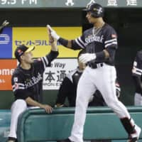 The Hawks' Yurisbel Gracial (right) is congratulated by pitcher Kodai Senga after hitting a solo homer in the eighth inning against the Lions on Thursday at MetLife Dome. Fukuoka SoftBank beat Seibu 3-2. | KYODO