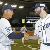 Lions pitcher Zach Neal shakes hands with manager Hatsuhiko Tsuji after their win over the Buffaloes on Wednesday in Tokorozawa, Saitama Prefecture. | KYODO