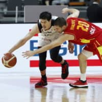 Japan's Yuta Watanabe (left) guards the ball against Montenegro's Nikoa Ivanovic on Monday at Dongguan Basketball Center in Dongguan, China. | REUTERS