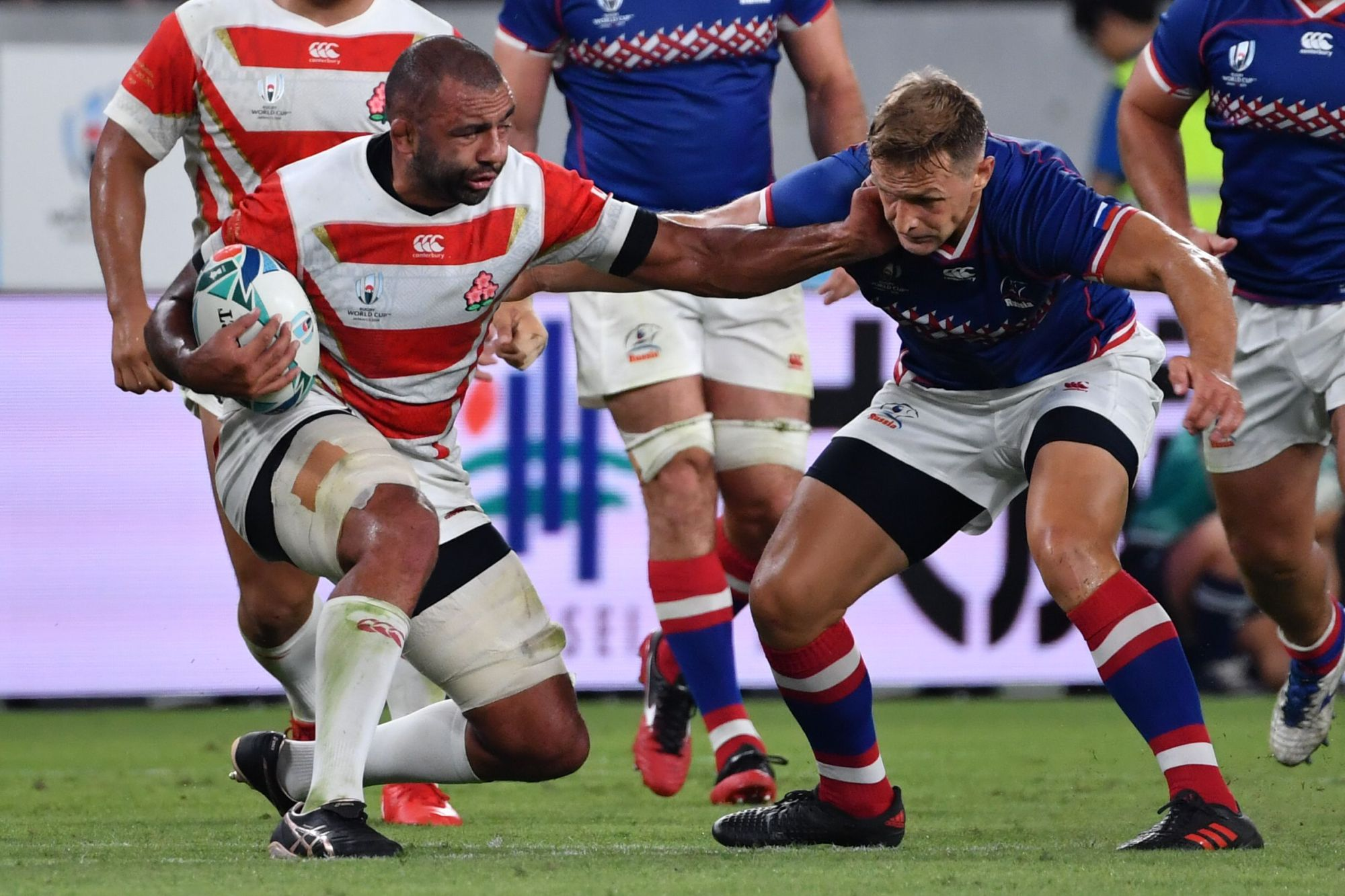 Japan's Michael Leitch (left) competes against Russia last Friday in the Rugby World Cup's opening match at Tokyo Stadium. | AFP-JIJI