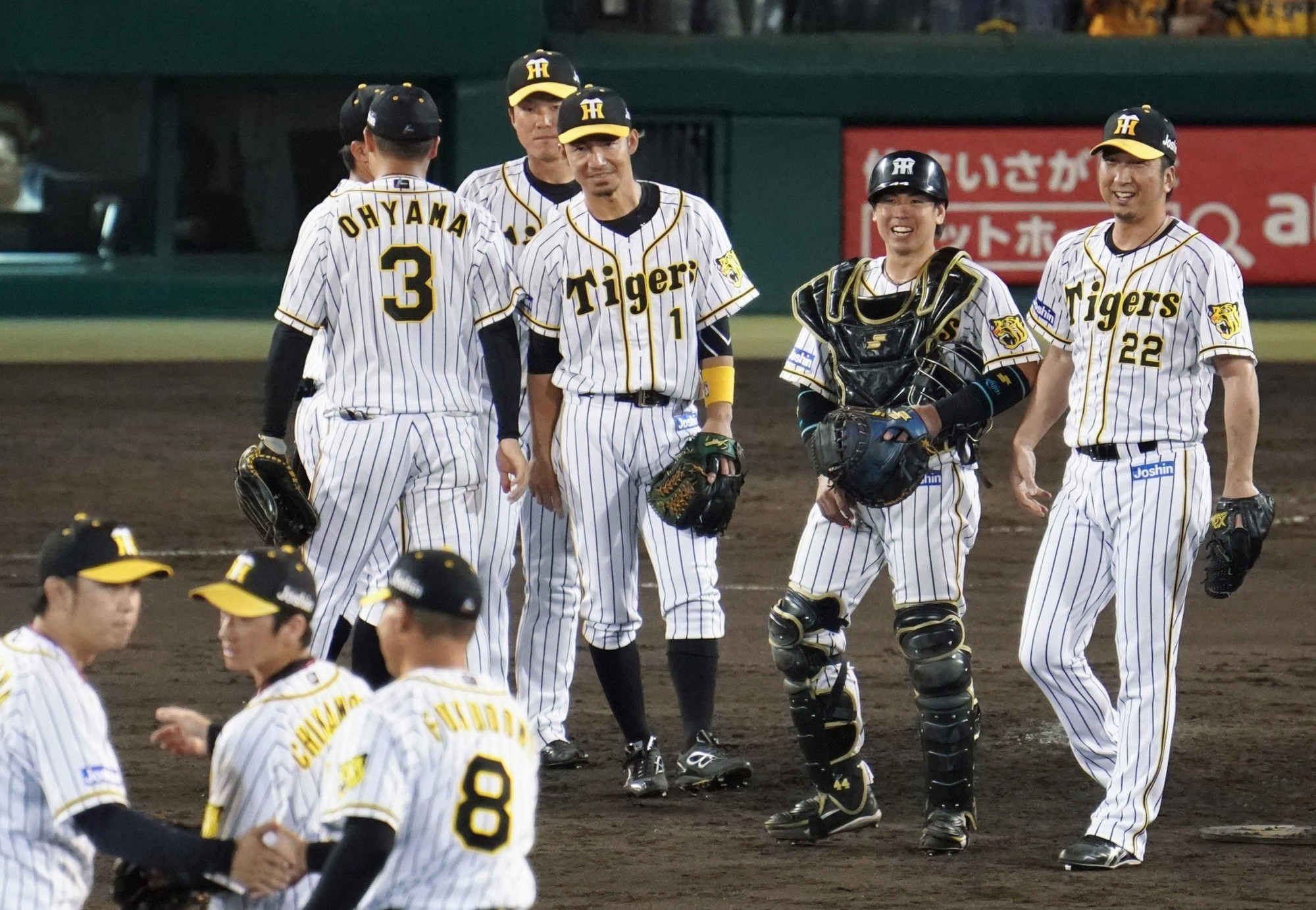 Tigers players celebrate their 3-0 win over the Dragons on Monday at Koshien Stadium. The result capped a six-game winning streak for Hanshin as it leapfrogged the Hiroshima Carp into third place and a spot in the Climax Series. | KYODO