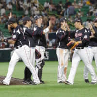 Lotte players celebrate their win over the Hawks on Monday at Yafuoku Dome. | KYODO