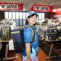 A volunteer in Kumagaya, Saitama Prefecture, shows off the uniform and backpack that will be used by 13,000 'Team No-Side' members during the 2019 Rugby World Cup.   KYODO