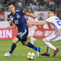 Japan's Maya Yoshida (left) and Paraguay's Miguel Almiron vie for the ball in second-half action on Thursday night.   KYODO