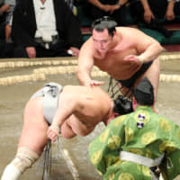 Yokozuna Kakuryu shoves down No. 1 maegashira Hokutofuji on the second day of the Autumn Grand Sumo Tournament on Monday at Tokyo's Ryogoku Kokugikan. | NIKKAN SPORTS