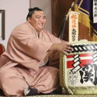 Autumn Grand Sumo Tournament champion Mitakeumi poses with a cask of sake on Monday at Dewanoumi stable in Sumida Ward. | KYODO