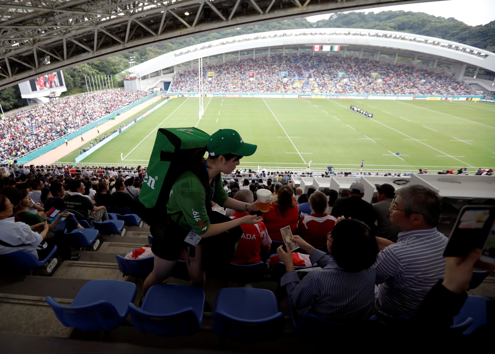 A beer vendor serves spectators at a Rugby World Cup match between Italy and Canada at Fukuoka Hakatanomori Stadium on Thursday. Wednesday's upcoming match between France and the United States could possibly be canceled as a result of Typhoon Mitag. | REUTERS