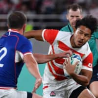 Japan's Ryohei Yamanaka carries the ball past Russia's Ramil Gaisin in a Rugby World Cup Pool A match on Friday at Tokyo Stadium.   AFP-JIJI