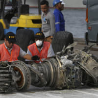 Officials inspect an engine recovered from the crashed Lion Air jet in Jakarta last November. On the anniversary of the first crash of a Boeing 737 Max, the CEO will begin two days of testimony before Congress by telling lawmakers that the aircraft company knows it made mistakes and is throwing everything into fixing the plane. | AP