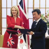 Foreign Minister Toshimitsu Motegi and British trade minister Liz Truss meet last month in Tokyo. | KYODO