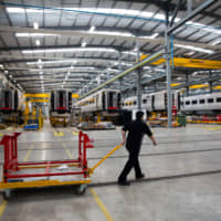 An employee pulls a trolley in front of train carriages being made at Hitachi Rail Europe Ltd.'s railway train vehicle manufacturing facility in Newton Aycliffe, northeast England, in 2017. | BLOOMBERG